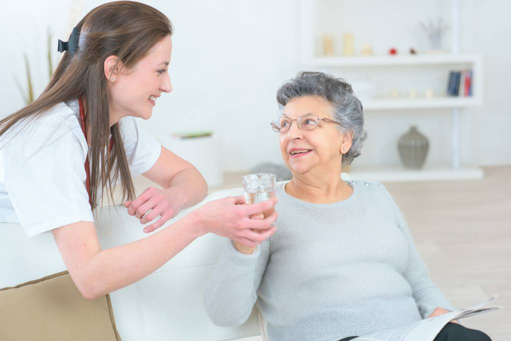 Caregiver-Giving-Water-to-Elderly-Woman