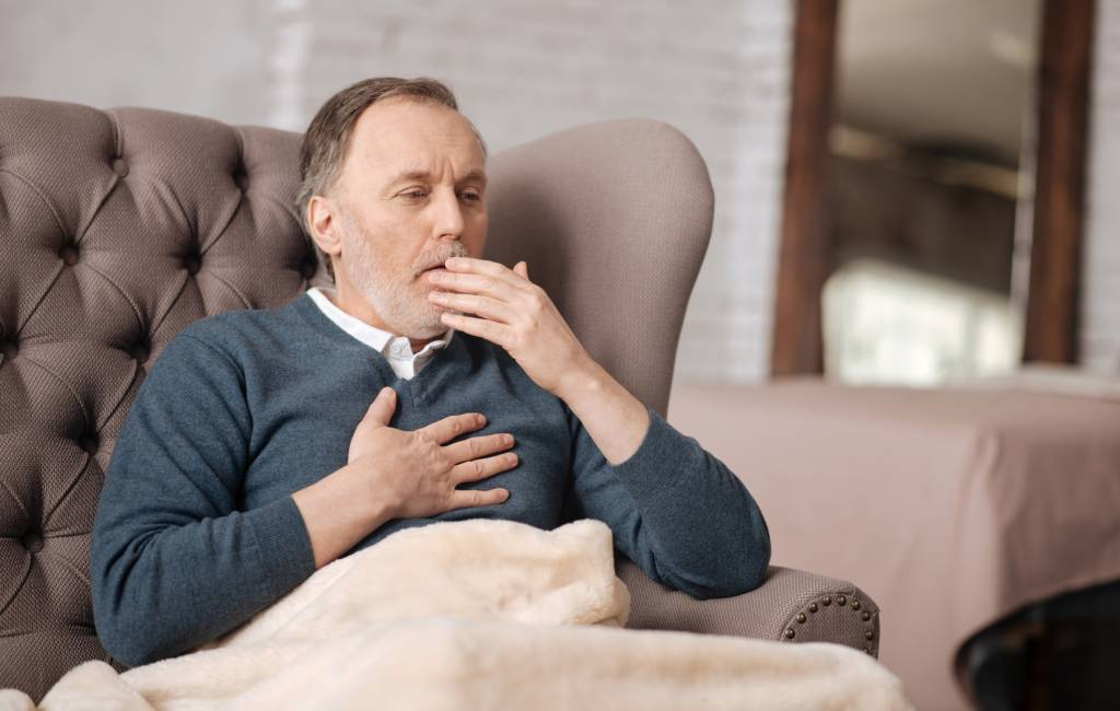 Old man sitting on couch and coughing
