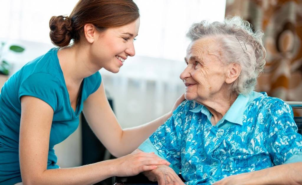 Caregiver Smiling and Meeting Senior