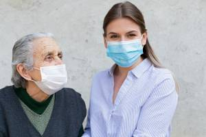 Caregiver with elderly ill woman wearing mask